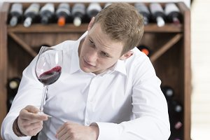 man shaking a red wineglass