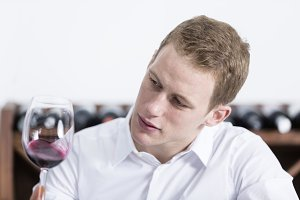 man shaking a red glass of wine.jpg