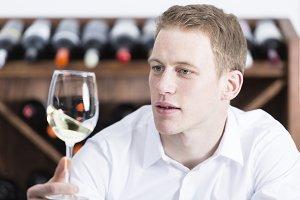 man shaking a white wineglass