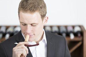 man smelling a cork stopper