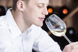 man smelling a white wineglass