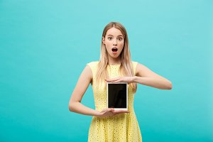 Excited shocked good-looking young woman in yellow dress having confused or puzzled expression on face while receiving urgent message or email, using wi-fi on tablet.