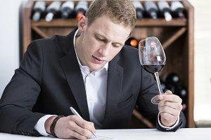 man writing on a wine tasting sheet