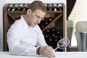 young man examining a wine glass