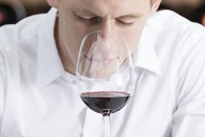 man smelling a red wineglass