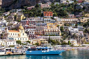 View from the sea to the Italian city with colorful houses on the mountains. Amalfi Coast - architectural and travel background
