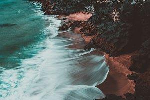 Orange and Teal Beach and Dark Rocks