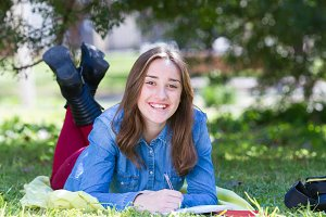 Teenager student girl lying in park