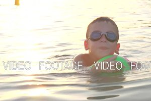 Boy with ball swimming in the sea at sunset