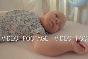 Newborn girl in crib before daytime sleep