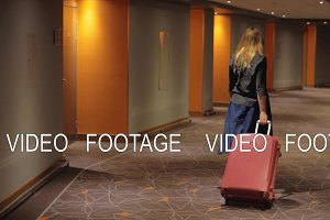 Woman with suitcase walking to the room in hotel corridor