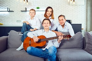 Happy family with guitar singing songs in the room.