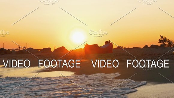 Man Relaxing In Inflatable Sunbed On The Beach At Sunset