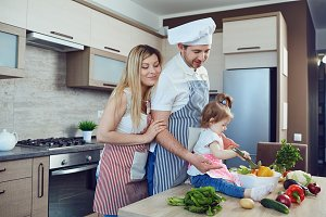 A happy family prepares food  in the kitchen.