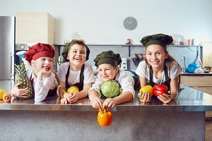 Funny children in the uniform of cooks on the table in vegetable