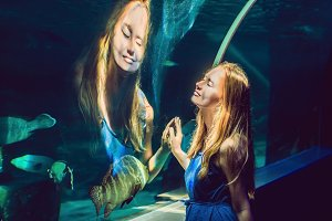 Young woman looking at fish in a tunnel aquarium