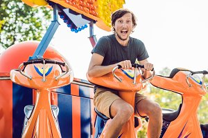Beautiful, young man having fun at an amusement park
