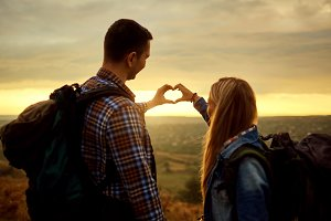 A couple of tourists with backpacks made a symbol of the heart w