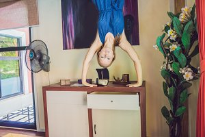 A woman is standing on his hands upside down in the living room