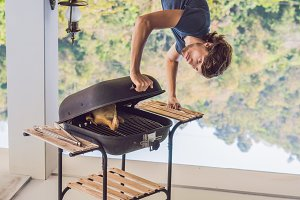 Handsome man preparing barbecue for friends standing upside down
