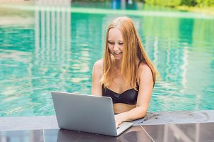 Young female freelancer sitting near the pool with her laptop in the hotel browsing in her smartphone. Busy at holidays. Distant work concept. Copy space for your text