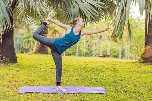 woman practicing yoga in a tropical park