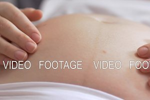 Expecting mother stroking belly with love and care