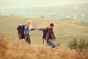 A young couple of tourists with backpacks are walking in nature