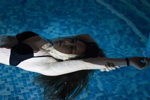 Beautiful young woman on water surface in swimming pool