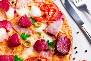Hot pizza with Pepperoni Sausage on a white table