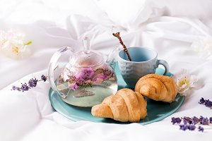 Breakfast in bed concept - french croissants with a cup of tea.