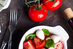 Caprese salad with mozzarella, tomato, basil and balsamic vinegar arranged on white bowl on stone background
