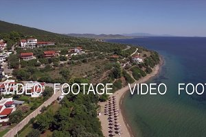 Flying over sea, cottages and resort on the coast. Trikorfo Beach, Greece