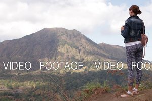 Young woman with smartphone and backpack on a beautiful mountain background. Volcano Batur, Bali.