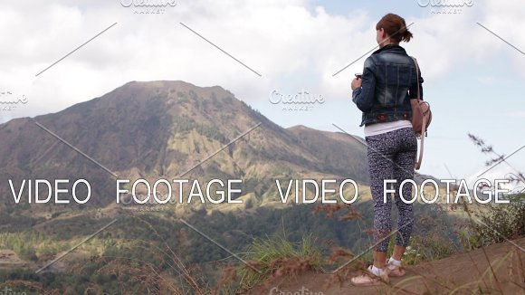 Young Woman With Smartphone And Backpack On A Beautiful Mountain Background Volcano Batur Bali