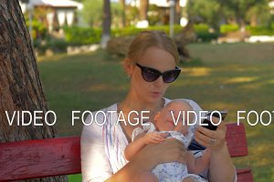 Woman using mobile during outing with baby in the park