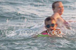 Boy having fun in water with mum