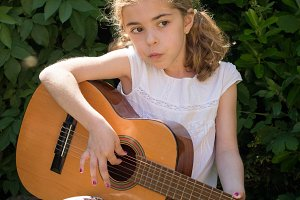 Little girl playing a spanish guitar