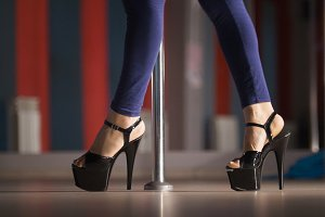 Slim female legs in black high-heeled shoes dancing on a pole dance