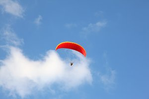 red parachute flies in  blue sky