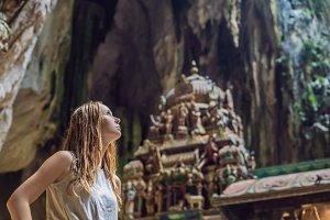 Young woman in the background of Batu Caves, near Kuala Lumpur, Malaysia. Traveling with children concept