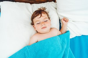 Adorable boy sleeping in bed