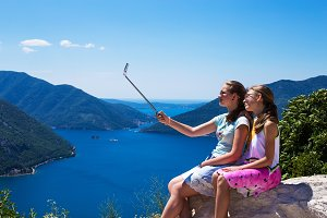Two teenage girls in the make photo on the phone and selfie sticks on the background of Boko Kotorska bay and mountains in Montenegro.