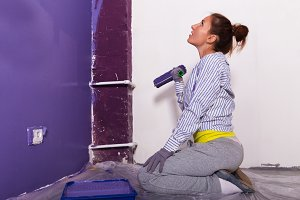 young attractive woman paints white wall with purple paint rolle