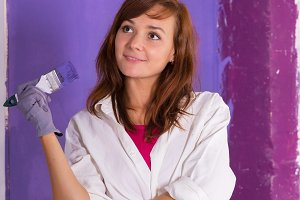 young attractive woman paints white wall with purple paint brush
