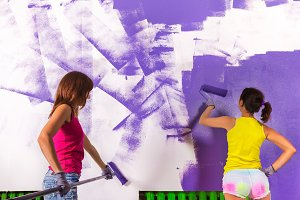 young beautiful women paints white wall with purple paint roller