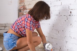 young attractive woman paints white brick wall and paint brush