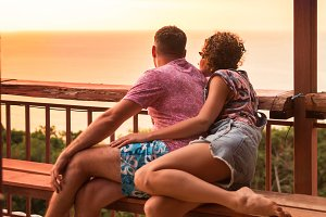 Young couple watches tropical exotic sunset