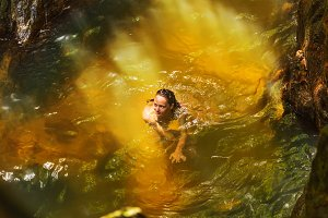 Young woman swimming in a natural tropical pool