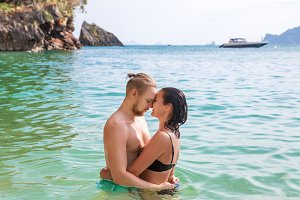 Young slim happy hipster couple on tropical beach kiss each other